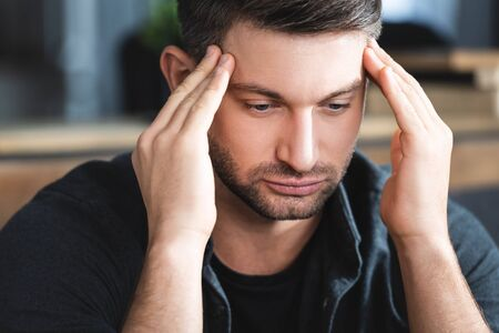 handsome man with headache touching head and looking down in apartment Reklamní fotografie