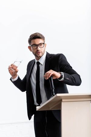 scared businessman in suit standing at podium tribune and holding glass of water during conference isolated on white
