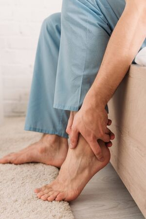 cropped view of man touching leg while suffering from pain in Achilles tendon