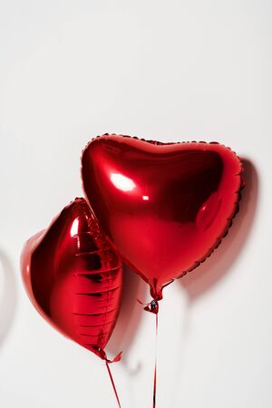 red and shiny heart shaped balloons on white Stock fotó