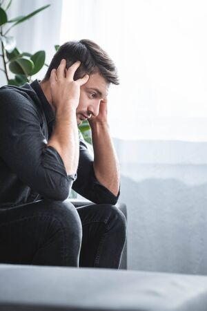 side view of handsome man with headache sitting on sofa in apartment