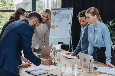 multicultural businesspeople looking at document on desk during business meeting
