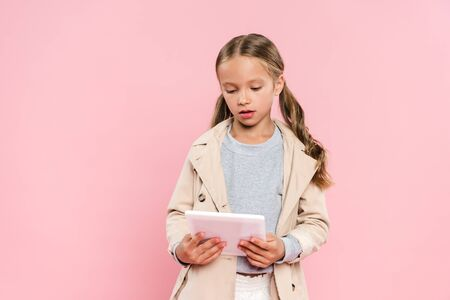 cute kid holding using digital tablet isolated on pink