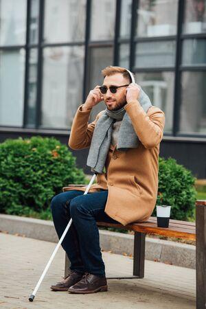 Blind man using headphones while sitting on bench Stockfoto