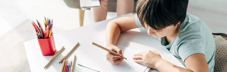 panoramic shot of kid with dyslexia drawing on paper with pencil