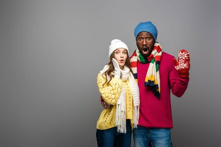 surprised interracial couple in winter outfit hugging on grey background