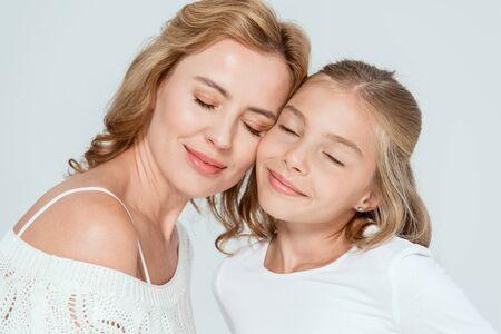 lachende moeder en dochter met gesloten ogen geïsoleerd op grijs