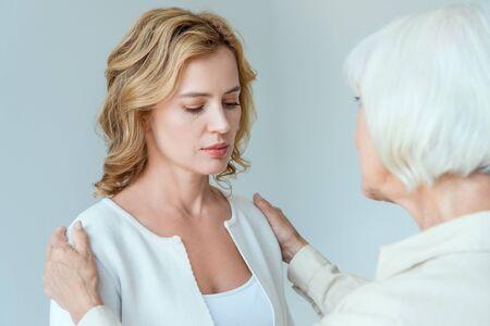 achteraanzicht van moeder knuffelen trieste dochter geïsoleerd op grijs