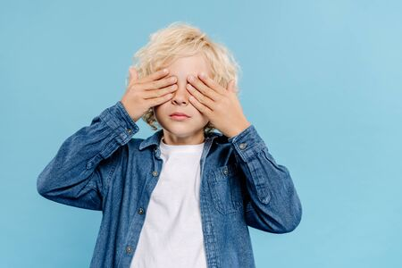 kid in denim shirt obscuring face isolated on blue