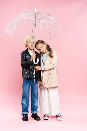 cute kids hugging and holding umbrella on pink background Foto de archivo