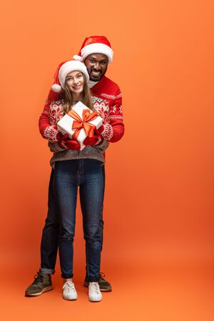 happy interracial couple in santa hats and Christmas sweaters hugging and holding gift on orange background Stock Photo