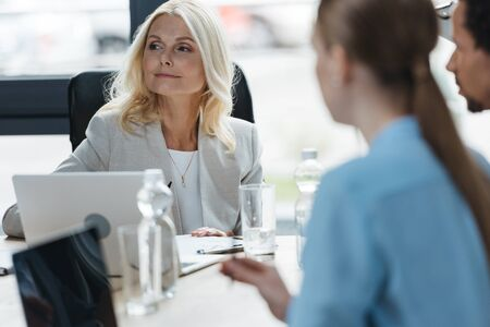 selective focus of confident businesswoman at business meeting with young multicultural colleagues
