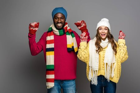happy interracial couple in winter outfit showing yes gesture on grey background