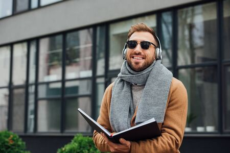 Smiling blind man in headphones holding book on urban street