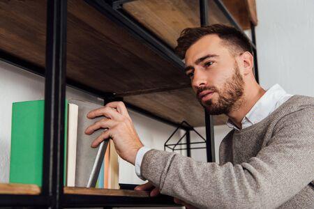 Blind man taking book from cupboard shelf