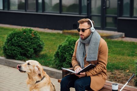 Blind man in headphones holding book on bench beside guide dog