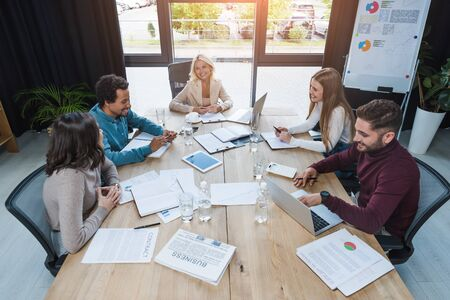 positive multicultural businesspeople sitting at wooden desk near digital devices, documents and glasses with water in meeting room