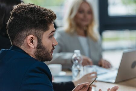 selective focus of young businessman talking at business meeting