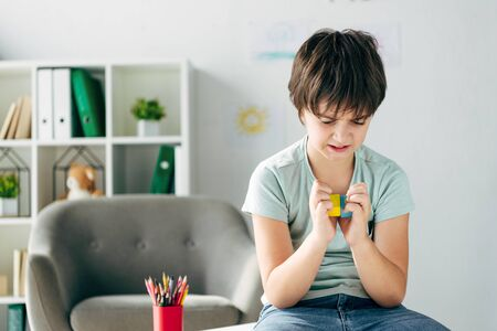 irritated kid with dyslexia holding wooden building blocks and looking at it