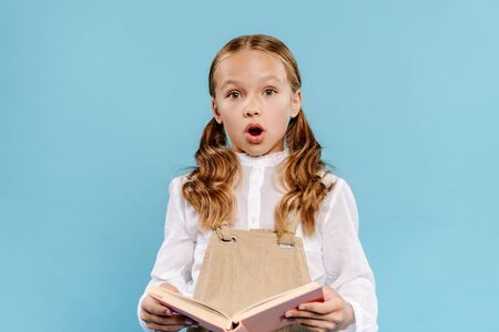 shocked and cute kid looking at camera and holding book isolated on blue