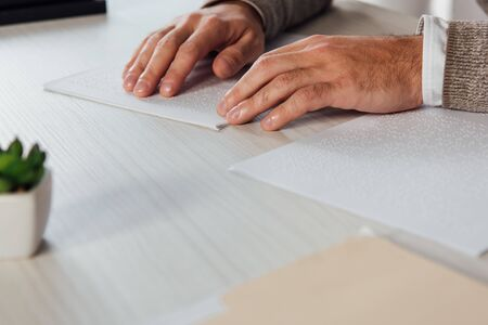 Cropped view of blind man reading braille font from paper at table