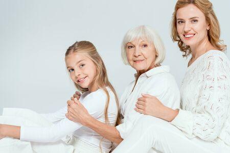 lachende kleindochter, moeder en grootmoeder knuffelen geïsoleerd op grijs