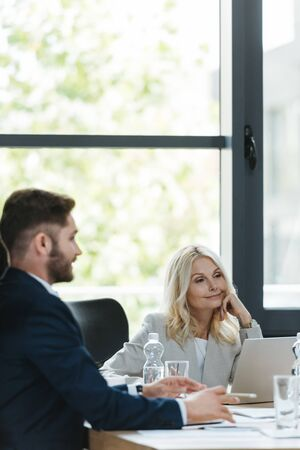 positive, attentive businesswoman listening to young colleague during business meeting