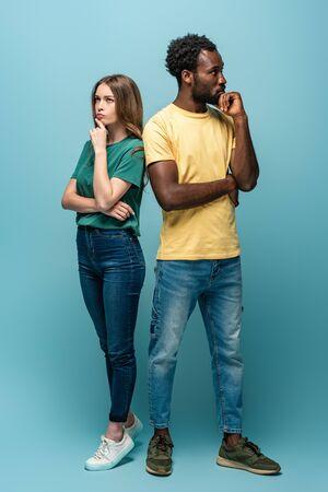 Vue sur toute la longueur d'un couple interracial réfléchi debout dos à dos sur fond bleu Banque d'images