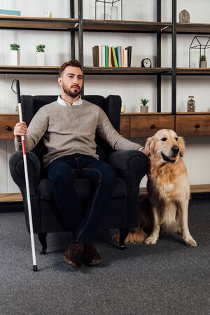 Blind man with walking stick sitting in armchair beside golden retriever