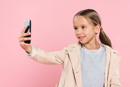 smiling and cute kid taking selfie isolated on pink Foto de archivo