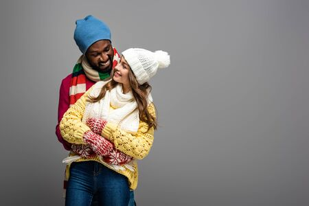 happy interracial couple in winter outfit hugging on grey background