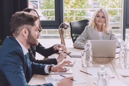 attentive businesswoman looking at young colleague talking at business meeting