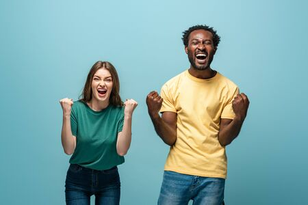 happy interracial couple showing yes gesture on blue background Stok Fotoğraf