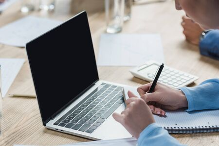 cropped view of businesswoman sitting near laptop and witing in notebook during business meeting