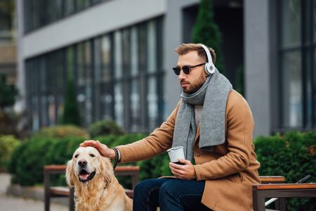 Blind man in headphones holding thermo mug and stroking guide dog in park