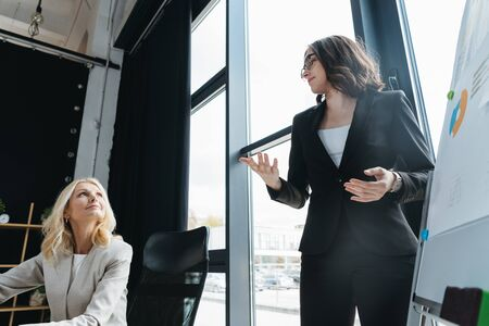 young manager talking to mature businesswoman while standing near flipchart and showing explain gesture