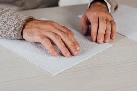 Cropped view of bind man reading braille font on paper at table