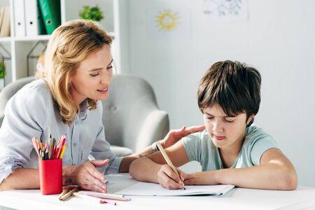 bambino con dislessia che disegna con la matita e lo psicologo infantile lo guarda