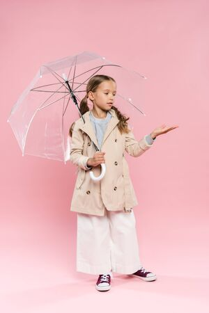 kid in autumn outfit with outstretched hand holding umbrella on pink background