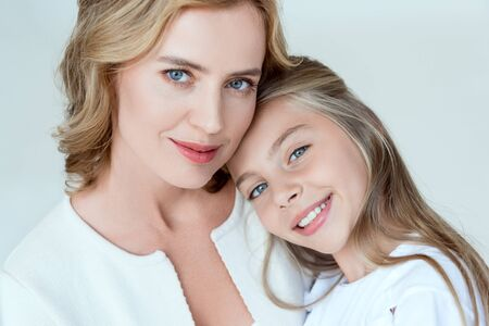 attractive mother and smiling daughter looking at camera isolated on grey Stock Photo