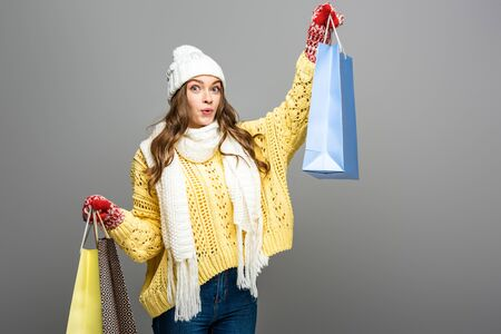 shocked woman in winter outfit with shopping bags on grey background