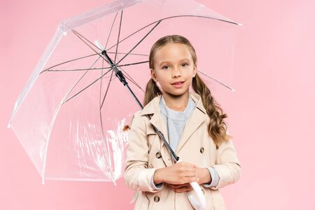 smiling kid in autumn outfit holding umbrella isolated on pink Stock Photo