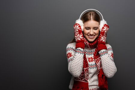 attractive laughing woman in christmas sweater, scarf, mittens and earmuffs, isolated on grey