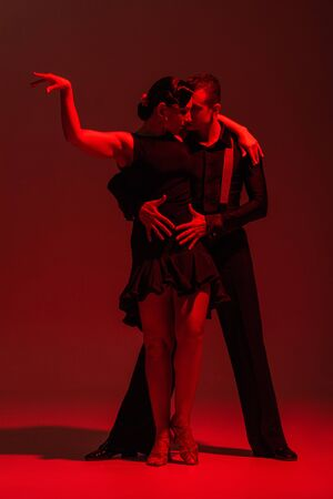 elegant couple of dancers in black clothing performing tango on dark background with red illumination Banque d'images