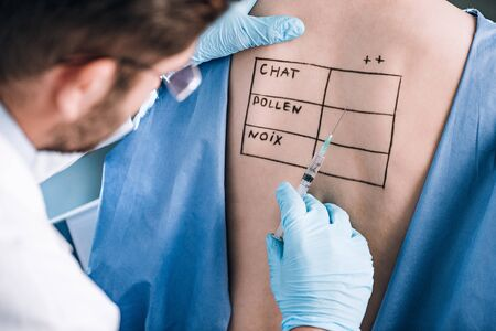 selective focus of allergist holding pipette near patient with letters on marked body