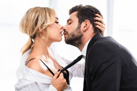 Side view of businesswoman pulling colleague tie while flirting in office