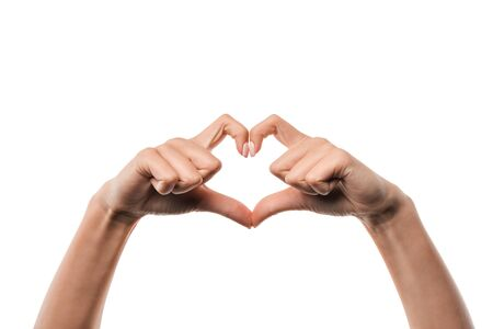 cropped view of woman showing heart-shape sign with fingers isolated on white