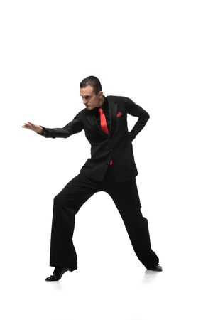 passionate tango dancer in elegant black suit inviting to dance on white background