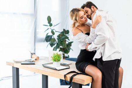 Sexy business couple taking off shirts on office table Reklamní fotografie