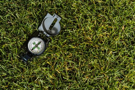 top view of retro compass on green grass